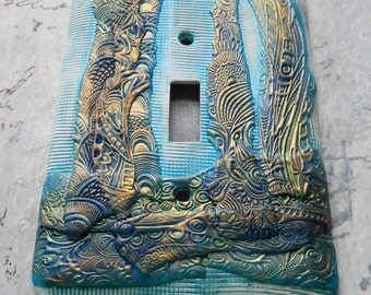 Blue Green and Gold switch plate cover, polymer clay, one of a kind, white background with teal, blue green and gold accents