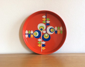 Vintage bright red  round metal serving tray with stylised  folk style floral decoration in blue, green and white