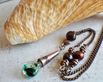 Bottle vial necklace filled with green oil bubbles on copper chain with copper color beads, fresh water pearls and a crystal element.