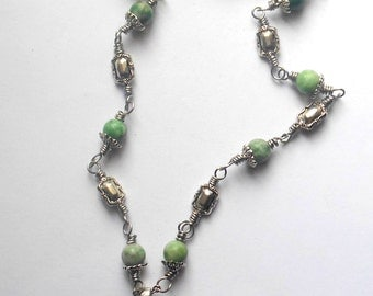Silver colour celtic knot, triquetra necklace with green jade beads.