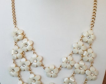 Three Strands of Beige Little Flowers with Crystal Clear Center Necklace.