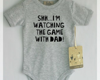 Shh..I'm watching the game with dad baby bodysuit. Modern baby clothes.