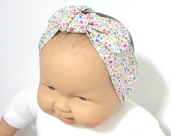 Baby headband with flowers with elastic at the back.