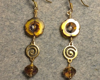 Translucent amber Czech glass pansy bead dangle earrings adorned with gold swirly connectors and amber Czech glass Saturn beads.