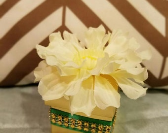 Elegant gold and green favor box with scented candle