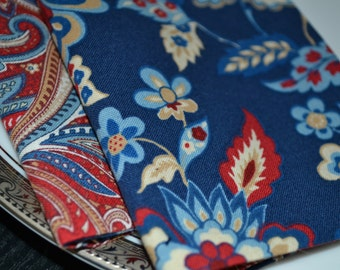 Set of 8 reversible cloth napkins featuring red, white, and blue paisley and flowers.