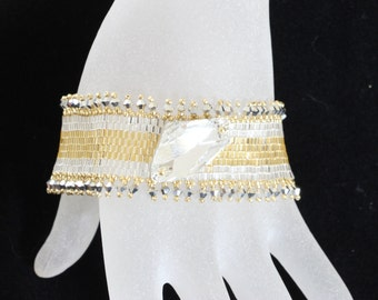 1080. Bead woven bracelet in silver and gold with crystal on top and  a toggle tube clasp.