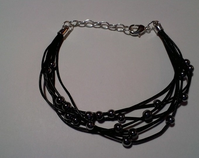 Bracelet made of black leather and gray or silver colored hematite beads