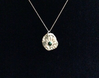 Shell print with synthetic green cabachon on a precious metal clay pendant.