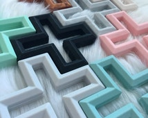 Geometric cross silicone teether with texture. Baby teething toy in copper, grey, white, pink, mint, seafoam and grey marble. BPA free.