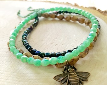 A three bracelet stack in natural and green tones with a bee charm