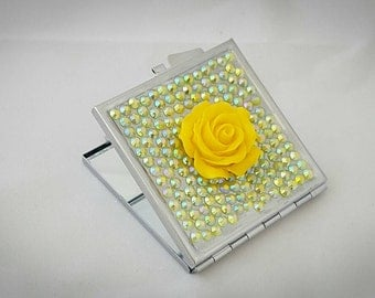 Square compact mirror in yellow with a flower
