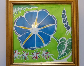 """Batik """"Morning Glory"""" flower, painted on silk, comes in a gold frame."""