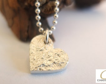 Good luck charms, heart I silver with structure of tree bark