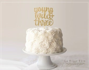 YOUNG, WILD + THREE gold glitter cake topper