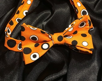 Orange polka dot pre-tied bow tie.