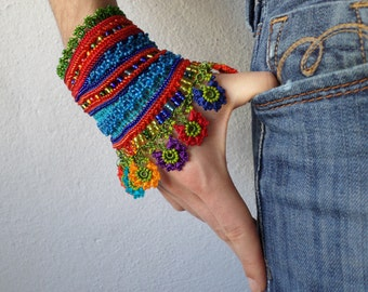 colorful beaded cuff bracelet with turquoise blue and bright red crocheted base and beaded crochet flowers in rainbow colors