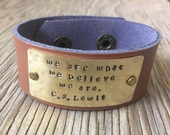 A riveted light brown leather cuff bracelet with hand stamped brass plate we are what we believe we are Handmade inspirational jewelry