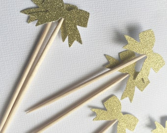 Set of 12 glittery gold bow cupcake toppers.