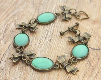 Bronze Tone Vintage Theme Mid Green and Bronze Bow Oval Link Bracelet Hand Painted Resin Glaze