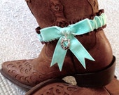 Country western garter in aqua velvet over brown satin with a rhinestone horseshoe charm.