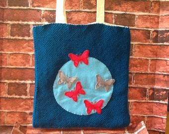 Blue hand knitted tote bag with appliqué butterfly design.