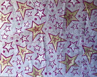 Sheet of white tissue paper linoprinted by hand with sparkly stars