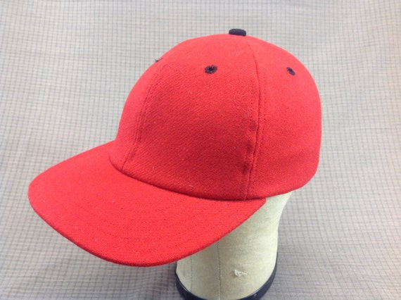 Handmade soft red wool flannel cap with black eyelets and button. Any size available, fitted or adjustable.