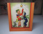 Adorable 1940's-50's colorful christmas card  boy and girl singing christmas carols holding a lantern with a cute dog holding holly berry
