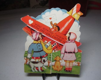 Art Deco die cut 1930's Valentine card pilot in airplane delivering valentine to two little girls with dogs