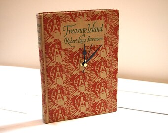 Treasure Island book clock with a pirate design cover in cream and red. Created using a vintage book published in 1957.