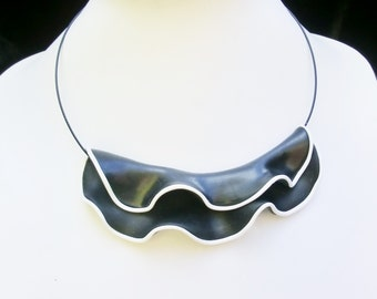 Swirly black and white choker necklace/ fold sculptured black Fimo (polymer clay) with white edge faulted over a nylon neck wire.