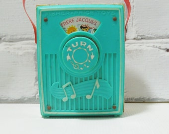Fisher Price Pocket Radio by Fisher Price. Frère Jacques. Circa 1960's-70's. Teal Blue Case. Red Strap. Yellow Backing.