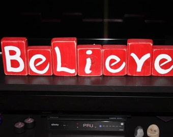 Christmas Believe wooden blocks in red and white colors with aged corners.