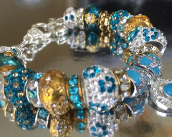 Turquoise, crystal, and gold charm bracelet.