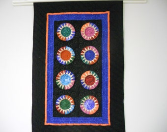 Modern sunburst quilted wall hanging in black and brights