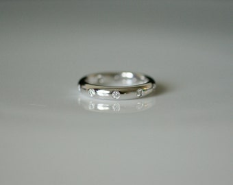 Solid 18K White Gold Band with Brilliant Cut Diamonds.