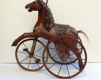 horse tricycle, Victorian velocipede horse is hand-carved from wood, leather saddle, wheels wood wrapped in iron and it has a horsehair tail
