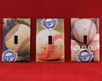 Kansas City (KC) Royals logo with baseball.  This is a handmade decoupaged light switch cover.