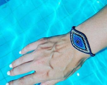 Large evil eye macrame bracelet in gold and blue colors.