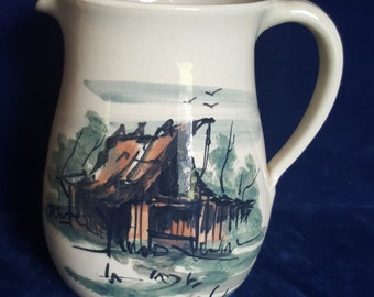 Large stoneware pitcher painted with red barn