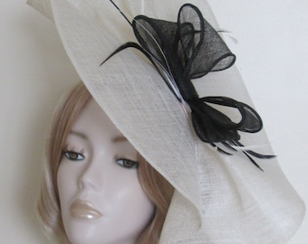 IVORY and BLACK FASCINATOR, With sinamay disc and bow, feathers, Mounted on a Ivory satin headband