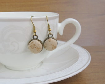 Antique bronze earrings and beige fabric.