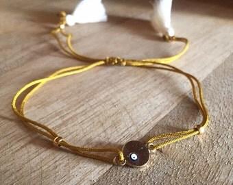 Mustard string bracelet with beige tassels and evil eye breloque