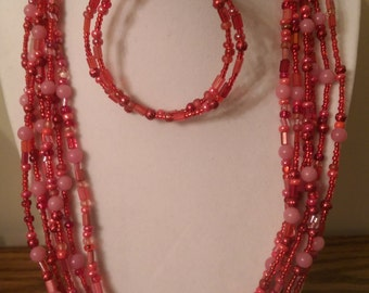 Red and pink multi-strand seed bead necklace and matching earrings.