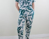 Vintage 80's white & teal jumpsuit, abstract tropical leaf pattern, short sleeved, lightweight fabric, comes with unattached shoulder pads