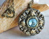 Music  box locket, round bronze locket with music box inside, and Turquoise Rivoli Crystal on cover