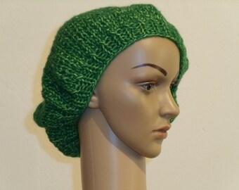 Knitted beret from green fleece yarn