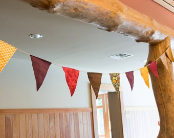 Fabric flag bunting / banners with mismatched fall colors and twine.