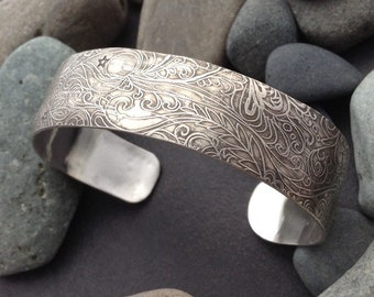 Sterling silver cuff bracelet, textured pattern with flowing night sky, leaves, vines, flowers, moon and stars, original drawing in metal